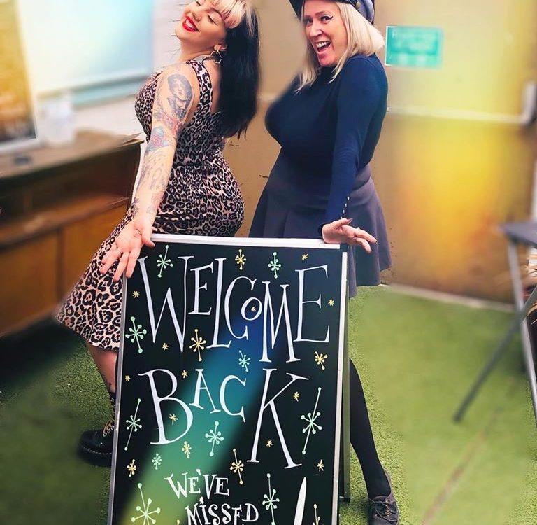 Night owl staff Jessie and Clare next to miss you sign